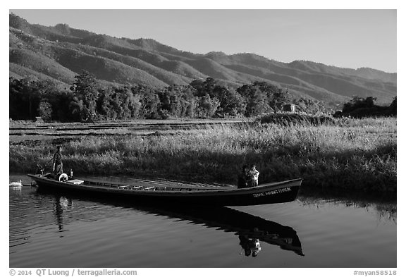 Woman riding with child in front of boat in Maing Thauk Village. Inle Lake, Myanmar (black and white)