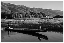 Woman riding with child in front of boat in Maing Thauk Village. Inle Lake, Myanmar ( black and white)