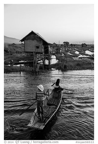 Children rowing across canal towards floating gardens, Maing Thauk Village. Inle Lake, Myanmar (black and white)