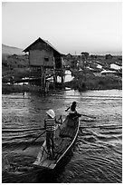 Children rowing across canal towards floating gardens, Maing Thauk Village. Inle Lake, Myanmar ( black and white)
