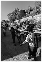 Vistor carried by porters on sedan chair,. Kyaiktiyo, Myanmar ( black and white)