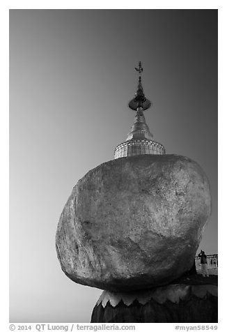 Pilgrim prays to the gleaming Golden Rock at sunset. Kyaiktiyo, Myanmar (black and white)