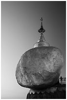 Pilgrim prays to the gleaming Golden Rock at sunset. Kyaiktiyo, Myanmar ( black and white)
