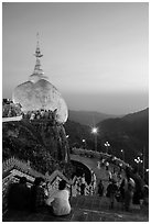 Pilgrims look at the Golden Rock from lower platform at sunset. Kyaiktiyo, Myanmar ( black and white)