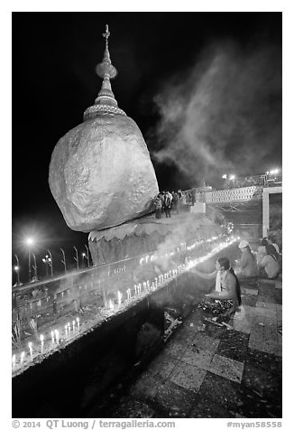 Offerings to the Buddha continues throughout the night at the Golden Rock. Kyaiktiyo, Myanmar (black and white)