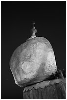 Pilgrims affix golden leaves to balancing boulder stupa at dawn. Kyaiktiyo, Myanmar ( black and white)