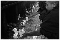 Monks lighting candles. Kyaiktiyo, Myanmar ( black and white)