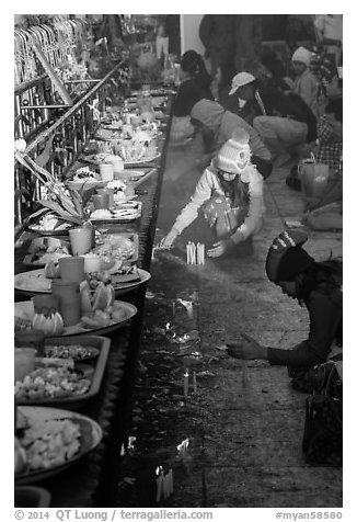 Morning food offering and pilgrims with cold weather hats. Kyaiktiyo, Myanmar (black and white)