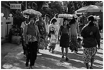 Women walk with platers of food on their heads. Kyaiktiyo, Myanmar ( black and white)