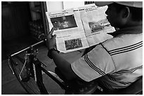 Cyclo driver looking at picture of QT Luong tour group in newspaper. Bago, Myanmar ( black and white)