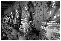 Monks sitting below row of buddha images, Wat Arun. Bangkok, Thailand ( black and white)
