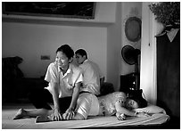 Traditional thai massage in traditional Thai medicine center of Wat Pho. Bangkok, Thailand ( black and white)