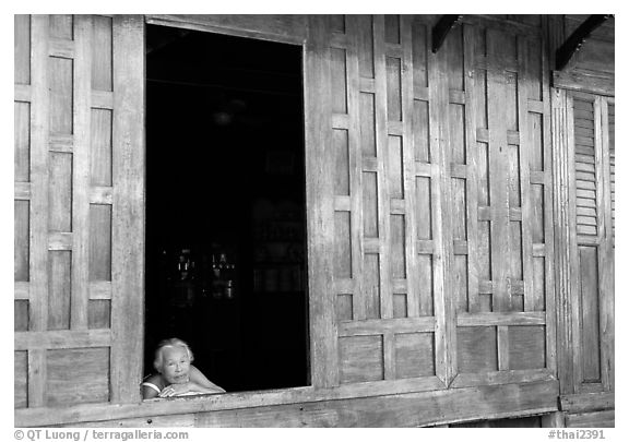 Woman looks out of teak house window. Damonoen Saduak, Thailand (black and white)