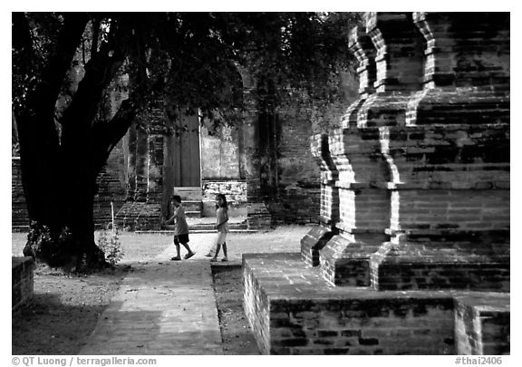Children walk among ruins of the King Narai's palace. Lopburi, Thailand (black and white)