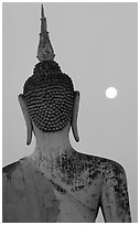 Moon and buddha image at dusk, Wat Mahathat. Sukothai, Thailand (black and white)