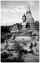 Classic sitting Buddha image and tiered, bell-shaped chedi. Sukothai, Thailand (black and white)