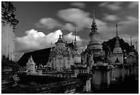 Chedis in blue light with bright clouds, Wat Suan Dok, dusk. Chiang Mai, Thailand (black and white)