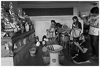 Worshippers with lotus inside Wat Saket. Bangkok, Thailand (black and white)