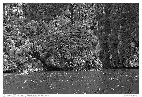 Couple paddling below steep cliffs. Krabi Province, Thailand (black and white)