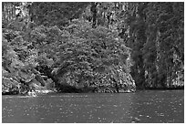 Couple paddling below steep cliffs. Krabi Province, Thailand ( black and white)