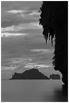 Limestone crag with stalactite, distant islet, boat light, Railay. Krabi Province, Thailand ( black and white)