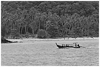 Longtail boat sailing in front of palm-fringed beach, Phi-Phi island. Krabi Province, Thailand (black and white)