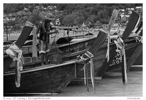 Row of boats, fisherman standing, Ko Phi Phi. Krabi Province, Thailand (black and white)