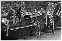 Row of boats, fisherman standing, Ko Phi Phi. Krabi Province, Thailand ( black and white)