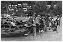 Women returning with shopping bags prepare to board boats, Ko Phi Phi. Krabi Province, Thailand (black and white)