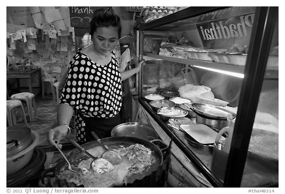 Woman adding spices to Pad Thai, Ko Phi-Phi island. Krabi Province, Thailand (black and white)