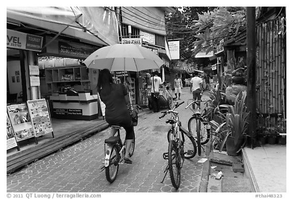 Woman riding bicycle with unbrella, Tonsai village, Ko Phi-Phi Don. Krabi Province, Thailand (black and white)