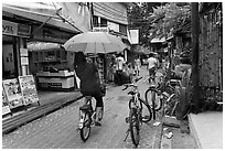 Woman riding bicycle with unbrella, Tonsai village, Ko Phi-Phi Don. Krabi Province, Thailand ( black and white)