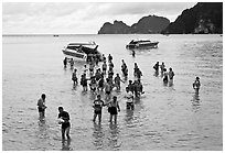 Asian tourists wading in water, Ko Phi Phi. Krabi Province, Thailand (black and white)