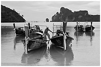 Man stepping on boats, Ao Lo Dalam, Ko Phi-Phi Don. Krabi Province, Thailand ( black and white)