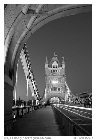 Walkway and road traffic on the Tower Bridge at night. London, England, United Kingdom (black and white)
