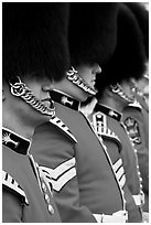 Guards with tall bearskin hat and red tunic standing in a row. London, England, United Kingdom (black and white)