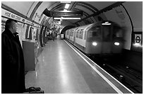 Man waiting for approaching train at Hyde Park subway station. London, England, United Kingdom ( black and white)