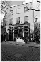 Cobblestone mews, pub, and man standing outside. London, England, United Kingdom (black and white)