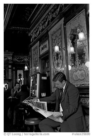 Man reading newspaper in front of etched mirrors, pub Princess Louise. London, England, United Kingdom (black and white)