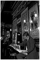 Man reading newspaper in front of etched mirrors, pub Princess Louise. London, England, United Kingdom ( black and white)