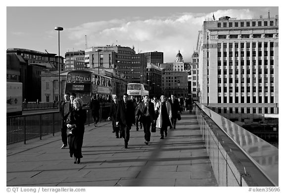 Office workers pouring out of the city of London across London Bridge, late afternoon. London, England, United Kingdom (black and white)
