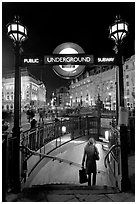 Woman with shopping bag entering subway at night, Piccadilly Circus. London, England, United Kingdom (black and white)