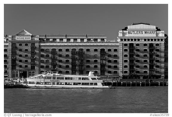 Butler Wharf and tour boat on the Thames. London, England, United Kingdom (black and white)