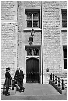 Yeoman Warder talking with man in suit in front of the Jewel House, Tower of London. London, England, United Kingdom ( black and white)
