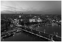 Aerial view of Charing Cross Station, Hungerford Bridge and Golden Jubilee Bridges at sunset. London, England, United Kingdom (black and white)