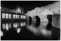 Pulteney Bridge, and quay reflected in River Avon at night. Bath, Somerset, England, United Kingdom (black and white)