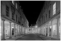 Street bordered by colonades at night. Bath, Somerset, England, United Kingdom (black and white)