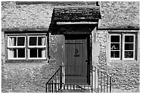 Windows and doorway entrance of stone house, Lacock. Wiltshire, England, United Kingdom ( black and white)