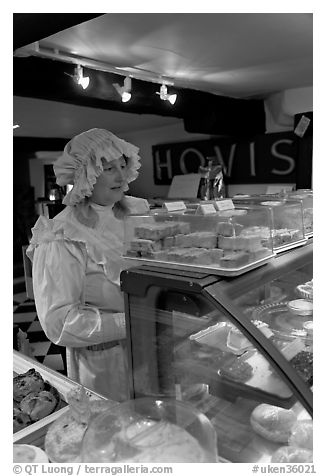 Woman wearing old-fashioned attire in a bakery, Lacock. Wiltshire, England, United Kingdom (black and white)