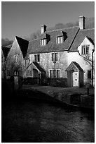Cotswold type cottages and Bybrook River, Castle Combe. Wiltshire, England, United Kingdom ( black and white)